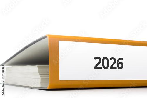 Fotografia  oranger Aktenordner gefüllt mit Papierseiten und Beschriftung 2026 liegend vor w