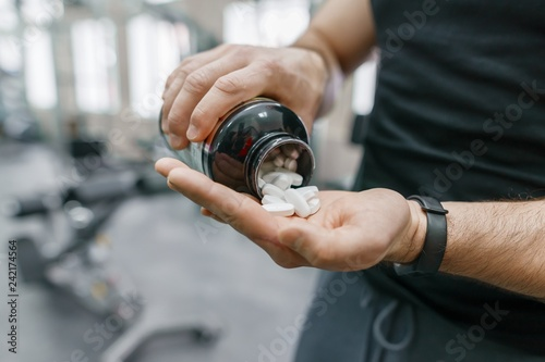 Fotografia  Closeup of sporty muscular man arms showing sports and fitness supplements, capsules, pills, gym background