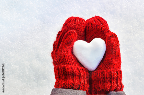 Obraz na plátně  Female hands in knitted mittens with heart of snow in winter day