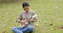 Woman Play With Ukulele In The...