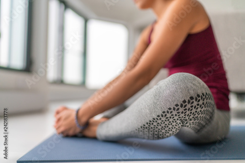 Yoga studio class woman stretching legs on exercise mat. Seated butterfly leg stretch holding soles of feet together with hands. Closeup on legs.