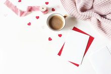 Valentines Day Or Wedding Still Life Scene. Cup Of Coffee, Envelope, Paper Hearts Confetti, Knitted Plaid And Blank Greeting Card Mockup On White Table Background. Love Concept. Flat Lay, Top View.