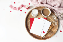Breakfast Still Life Scene. Cup Of Coffee, Gypsophila Flowers, Paper Hearts Confetti, Candle And Blank Greeting Card Mockup On Wooden Tray. Valentines Day, Wedding Or Love Concept. Flat Lay, Top View.