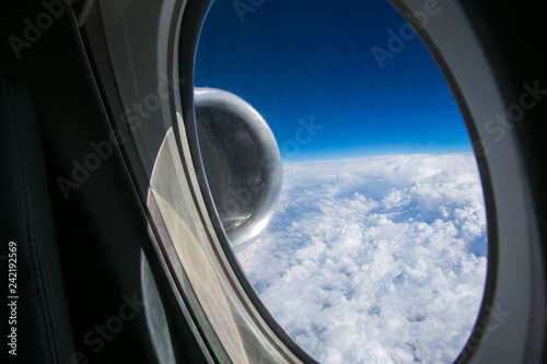 View from the window of the plane onto the wing and engines of a fokker 100 model with a blue sky and white clouds Canvas Print