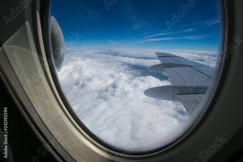 View from the window of the plane onto the wing and engines of a fokker 100 model with a blue sky and white clouds Wallpaper Mural