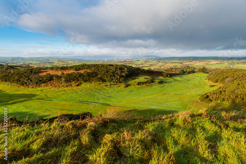 Eary morning golden hour light reveals a lush green golf course with a rolling landscape of grass and fields in the distance on the Ards Peninsula, County Down, Northern Ireland