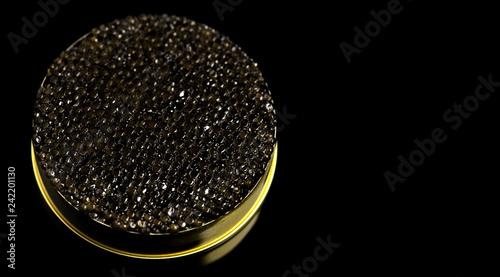 Black caviar closeup. Black caviar in tin can on black background. Delicatessen