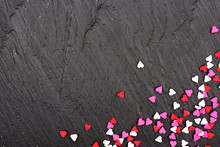Corner Border Of Valentines Day Candy Heart Sprinkles Over A Black Textured Background