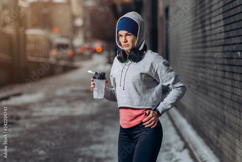 Fotografia  Fit woman drinking protein shake on winter day in city