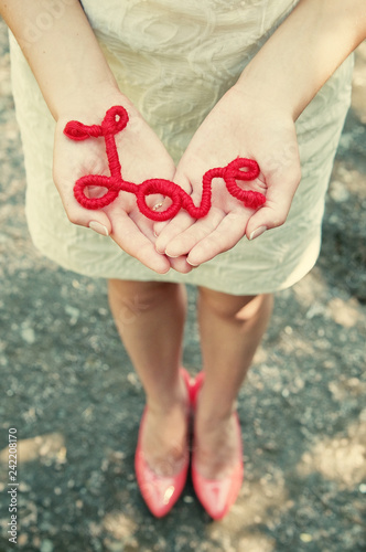 Photo  The girl in a white dress holds in hands a red inscription love made from thread