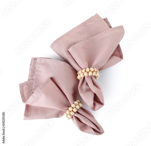 Fabric napkins with decorative rings for table setting on white background
