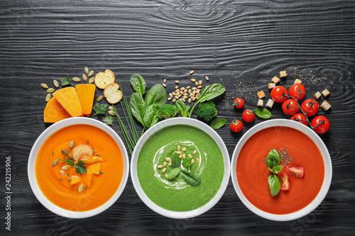 Flat lay composition with various soups and ingredients on wooden background. Healthy food