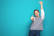 Happy young woman showing thumbs up on color background, space for text. Celebrating victory