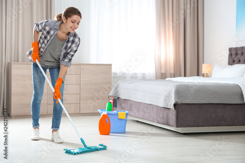 Fotografia Young woman washing floor with mop in bedroom, space for text
