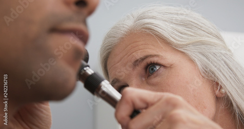 Close up of senior female medical doctor using otoscope to examine patients ear Canvas Print