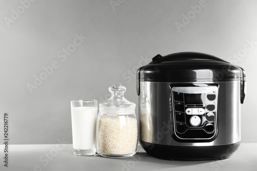 Modern powerful multi cooker and products on table against grey background. Space for text