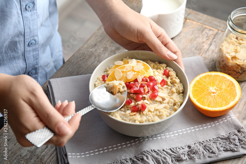 Woman eating quinoa porridge with nuts, orange and pomegranate seeds at table, closeup. Tasty breakfast