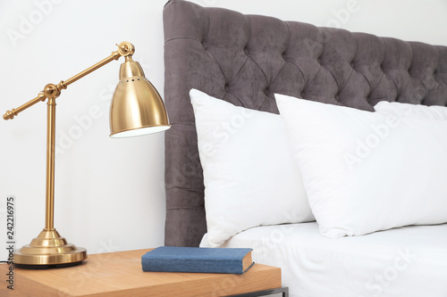 Comfortable bed and nightstand in modern room interior Wallpaper Mural