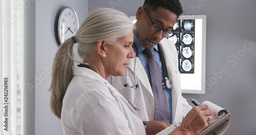 Photo Senior female doctor taking notes of patients ct scan while consulting with young colleague