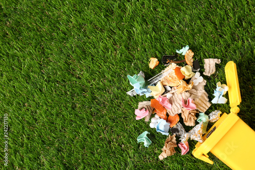 Trash bin and different garbage on green grass, top view with space for text Canvas Print