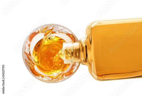 Pouring expensive whiskey into glass on white background, top view
