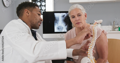 Fotografie, Tablou Senior female patient consulting with young doctor about back injury