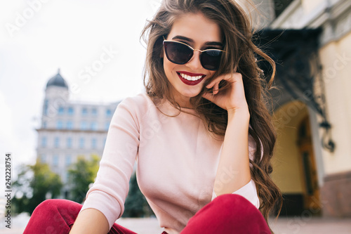 Cuadros en Lienzo Buttom view of attractive girl in sunglasses with snow-white smile, long hairstyle and vinous lips chilling in city