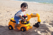 Asian Boy Play A Toy Of Excavator With A Sand