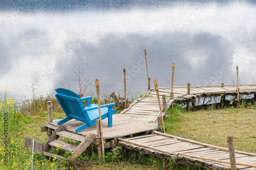 Foto  Scenic view landscape of blue chair and lake.