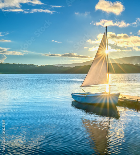 Lonely sailboat in the beautiful sunset with sun stars shines from sky and the surface of the lake is calm and peaceful when watching them
