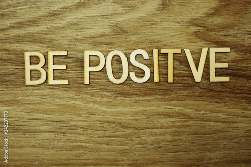 Photo  Be Positive text message on wooden background