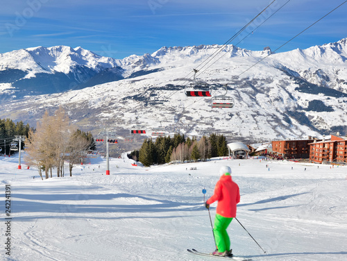 skier on ski slopes in french alps resort and chair lift under blue sky