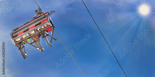 people in ski lift seen from below under sunny blue sky
