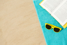 Vacation, Travel And Summer Holidays Concept - Yellow Sunglasses And Book On Blue Beach Towel On Sand