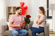 valentines day, couple, relationships and people concept - happy man giving woman flowers and present at home