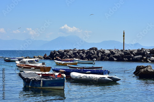 Fotografía  Small recreational and fishing boats moored in calm water behind artificial breakwall made of free laid stones on Mediterranean coast