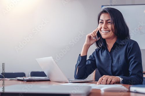 Businesswoman in black shirt talking by mobile phone in office