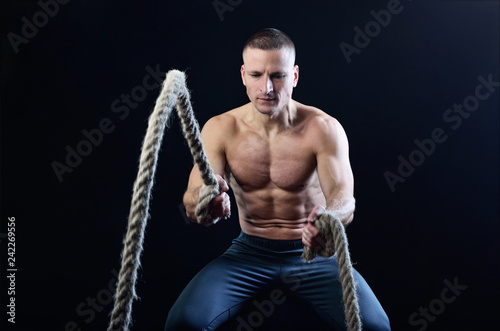 Fotografie, Obraz  Young muscular man dynamically workout with battle rope