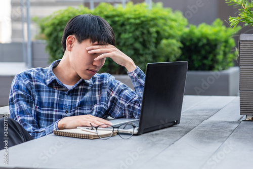 Fotografie, Obraz  stressed asian freelance man working on laptop at outdoor workplace