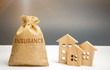 A bag with money and the word Insurance and wooden houses. The concept of property insurance and housing. Accumulation of money for home insurance, health and life. Risks