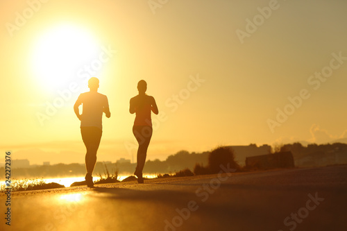 Fotografia  Couple practicing sport running at sunset on the road