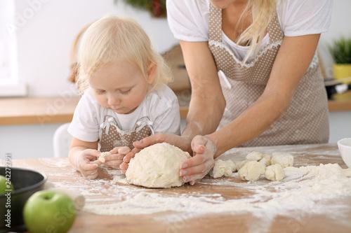Plakat Mała dziewczynka i jej blondynki mama w beżowych fartuchach bawić się i śmia się podczas gdy ugniatający ciasto w kuchni. Domowe ciasta na chleb, pizzę lub upiecz ciasteczka. Rodzinna zabawa i gotowanie koncepcji