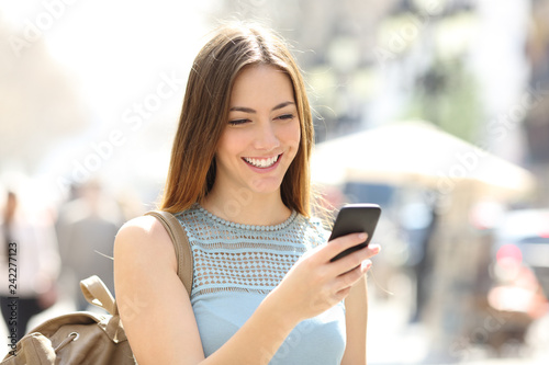Happy girl walking in the street checking phone