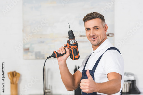 Carta da parati selective focus of smiling adult repairman holding drill in hand and showing thu