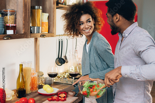 Vegetarian african-american couple cooking salad in kitchen Canvas