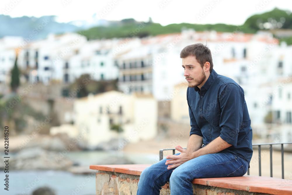 Fototapeta Worried man looking away sitting on a ledge