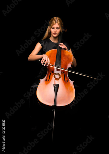 Canvas Young girl playing the cello on isolated black background