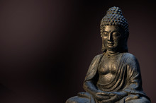 Buddha Statue Sitting In Meditation Pose Against Deep Dark Background.