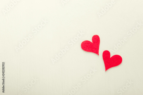 Two red fabric hearts applique on white background. top view flat