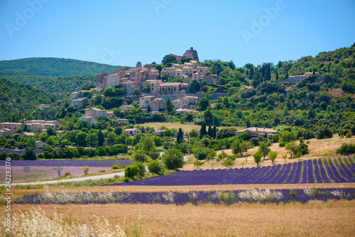 Tuinposter Lavendel City of Saint-Saturnin-les-Apt on the hill with lavender fields in valley on summer day. Provence, France